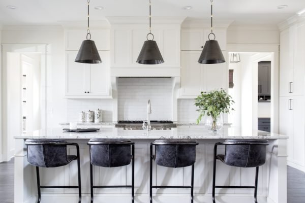 Clean white kitchen design with dark fixtures and bar stools